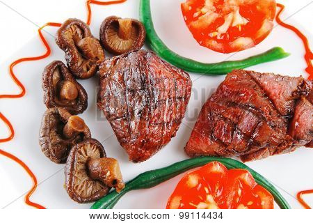 served grilled beef fillet mignon entrecote on a white plate with mushrooms and tomatoes on plate isolated on white background