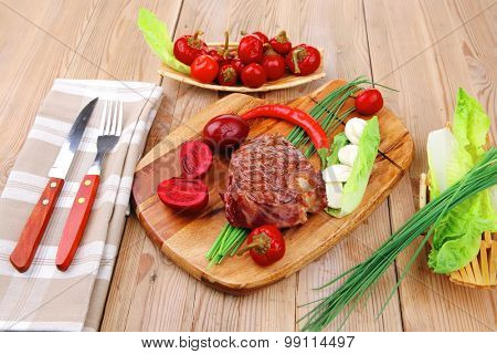 bbq : beef (pork) steak garnished with green staff and red chili hot pepper on wooden table with cutlery