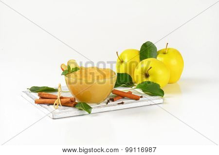 bowl of apple sauce, apples and spice on wooden cutting board