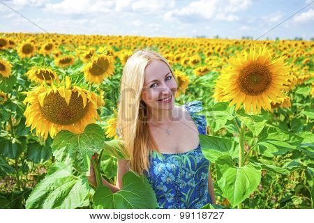 Close up portrait of a beautiful young girl in blue dress on a background field of sunflowers