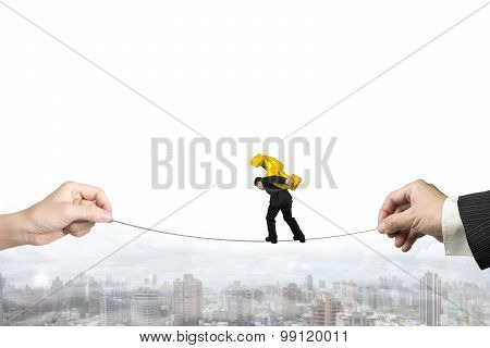 Businessman Carrying Dollar Sign Balancing Tightrope With Hands Holding