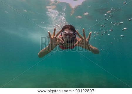 Freediver woman descends into water, showing