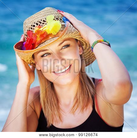 Portrait of beautiful girl on the beach, wearing sun hat with colorful flowers decoration, having fun on beach party, happy summer holidays