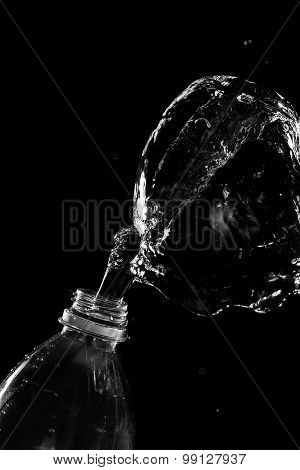 Large Stream Of Water On Black Background Departs From Plastic Bottle