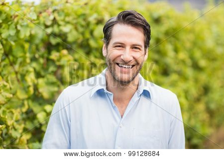Young happy man smiling at camera in the grape fields