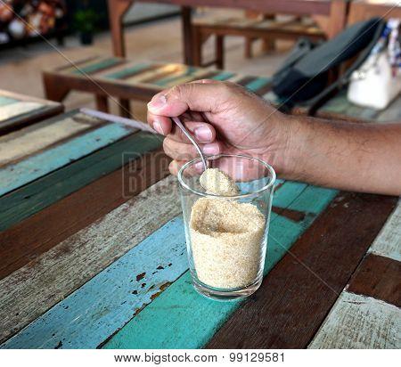 Hand Holding Teaspoon With Sugar