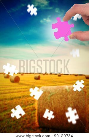 Hand holding jigsaw piece against blue sky over fields with hay bales