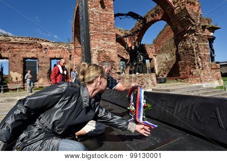 ORESHEK FORTRESS, LENINGRAD OBLAST, RUSSIA - AUGUST 15, 2015: Organizers laying flowers to the monument to the defenders of the fortress Oreshek during the River marathon Oreshek Fortress race
