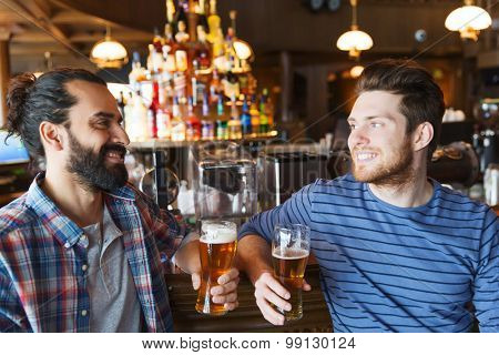 people, leisure, friendship, communication and bachelor party concept - happy male friends drinking beer and talking at bar or pub