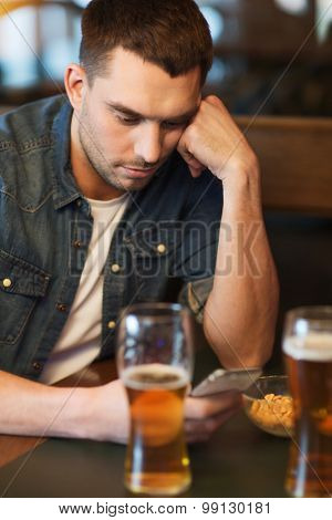 people and technology concept - man with smartphone drinking beer and reading message at bar