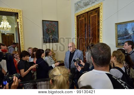 ST. PETERSBURG, RUSSIA - AUGUST 13, 2015: Deputy Director of the Russian Museum for capital construction and restoration Vladimir Bazhenov talk with press in restored interiors of the Marble Palace