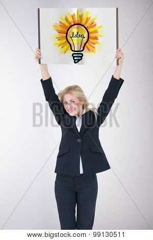 Businesswoman showing a book against grey background