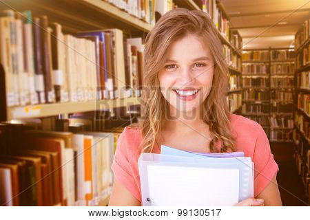 Smiling hipster holding notebook against close up of a bookshelf