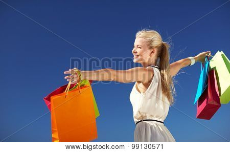 consumerism, sale and people concept - smiling woman with shopping bag rising hands