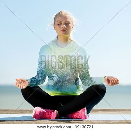 sport, fitness, yoga, double exposure and people concept - happy young woman meditating in lotus pose over blue sky with sea and tree background