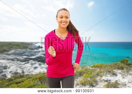fitness, sport, training and people concept - smiling african american woman running outdoors over beach background