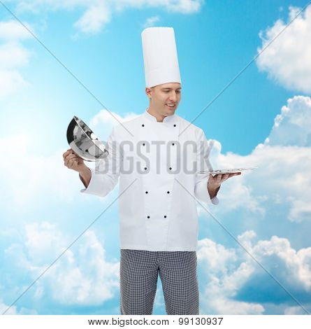 cooking, profession and people concept - happy male chef cook opening cloche cover over blue sky with clouds background