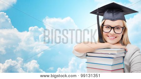 education, high school, knowledge, and people concept - picture of happy student girl or woman in trencher cap with stack of books over blue sky and clouds background