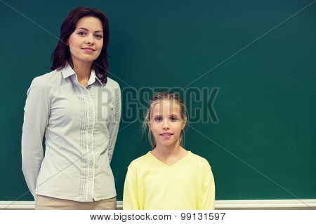education, elementary school, learning and people concept - little school girl with teacher at green chalkboard in classroom