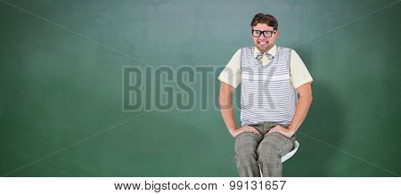 Geeky hipster sitting on stool against green chalkboard