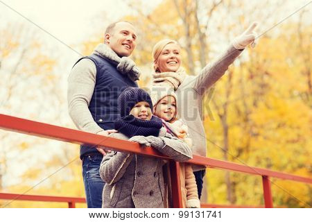 family, childhood, season and people concept - happy family pointing finger in autumn park