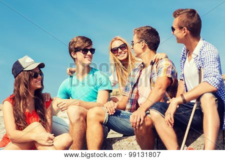 friendship, leisure, summer and people concept - group of smiling friends with skateboard sitting on city street