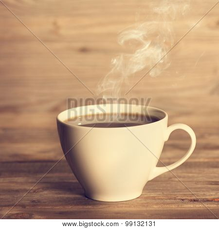 Steaming coffee in white cup in soft focus setting with dramatic ambient light, over dark wooden background in vintage style.