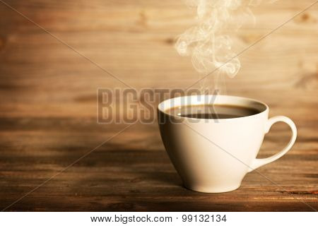Steaming coffee in white cup in soft focus setting with dramatic ambient light, over dark wooden background.
