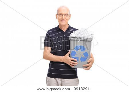 Senior gentleman holding a recycle bin full of shredded paper and looking at the camera isolated on white background