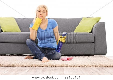 Young woman with cleaning gloves holding a spray bottle and sitting on the floor in front of a gray sofa isolated on white background