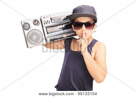Little boy in hip-hop outfit carrying a ghetto blaster and holding finger on his lips isolated on white background