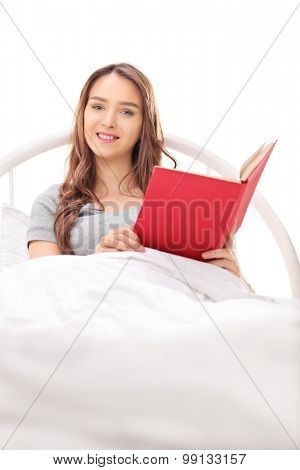 Vertical shot of a young brunette woman lying in bed covered with a white blanket and holding a book isolated on white background