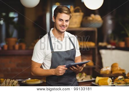 Portrait of a handsome waiter holding a tablet at the coffee shop