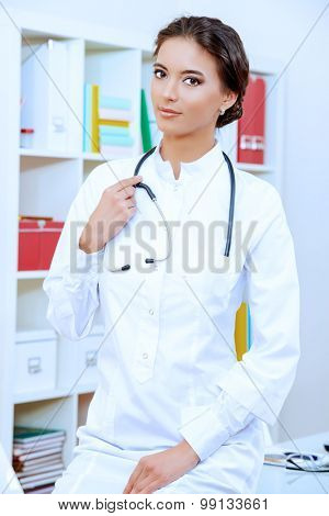Smiling female doctor in white coat looking at camera. Medicine, healthcare.