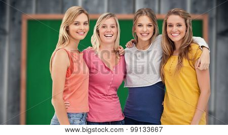 Four friends standing beside each other and smiling against blackboard with copy space on wooden board