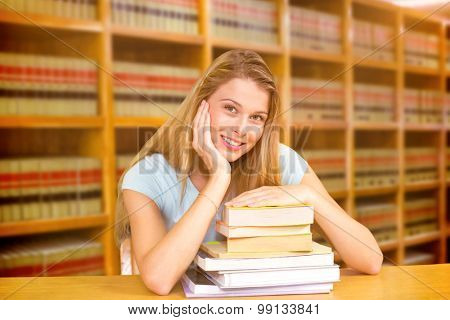 Portrait of female student in library against close up of a bookshelf