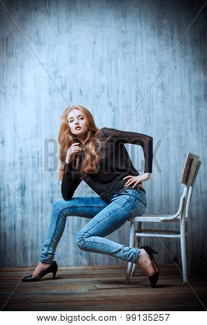 Beautiful blonde girl in jeans clothes posing by the grunge wall. Fashion.