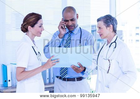 Concentrated doctor showing file to his colleagues while calling in the hospital