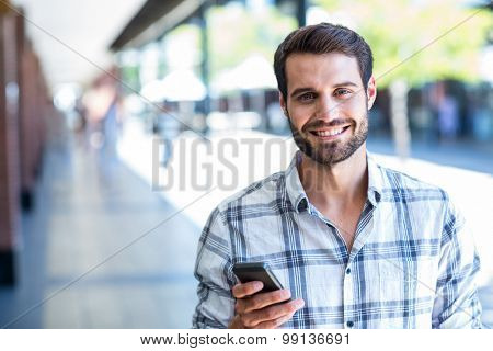 Hipster man using his smartphone in the city on a sunny day