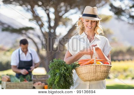 Blonde woman holding a vegetables basket at the local market