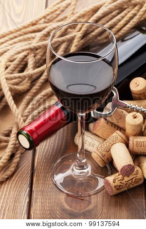 Glass of red wine, bottle and corks on rustic wooden table