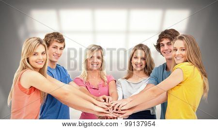 Friends standing around each other as they stack their hands against room with large window showing city