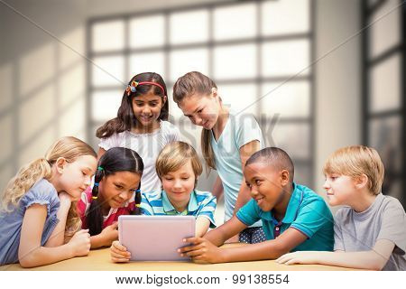 Cute pupils using tablet computer in library against room with large window showing city