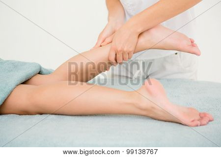 Masseur massaging womans leg at spa center