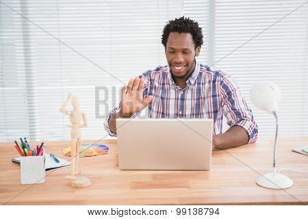 Young businessman waves at his laptop in the office
