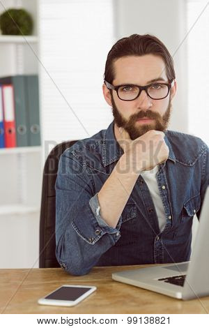 Hipster businessman working on his laptop in his office
