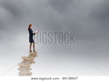 Young businesswoman on pile of old books with red book in hands