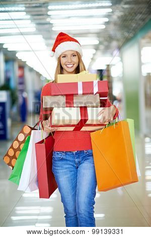 Woman leaving shopping mall with gift boxes