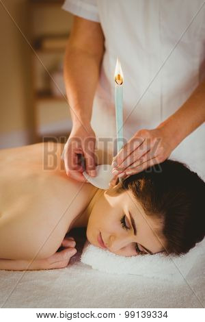 Young woman getting ear candling treatment in therapy room