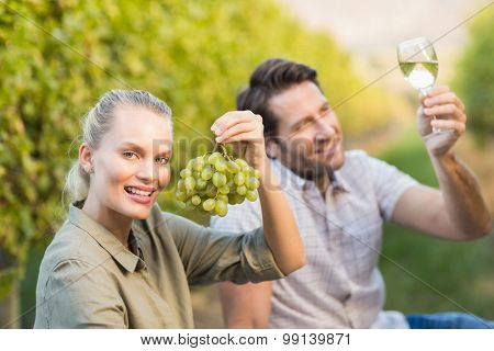 Two young happy vintners holding a glass of wine and grapes in the grape fields